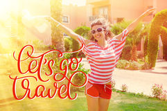 Happy young woman raising her hands in the summer park and text Lets go travel. Calligraphy lettering hand draw Stock Image