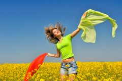 Happy young woman on rape field Stock Photography