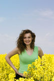 Happy young woman in rape flower field Stock Image