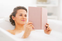 Happy young woman reading book in bathtub stock image