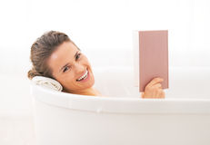 Happy young woman reading book in bathtub Royalty Free Stock Image