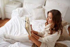 Happy young woman reading book in bed at home Royalty Free Stock Images