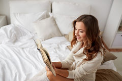 Happy young woman reading book in bed at home Royalty Free Stock Photography