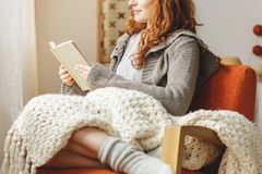 Woman reading a book. Happy young woman reading a book in a chair Royalty Free Stock Photo