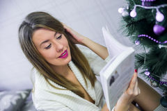 Happy young woman reading book in front of Christmas tree. Christmas evening. Young beautiful blonde woman read book Royalty Free Stock Image