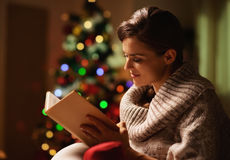 Happy young woman reading book in front of christmas tree Royalty Free Stock Images