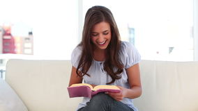 Happy young woman reading a book stock video