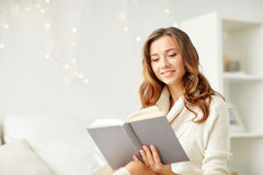 Happy young woman reading book at home Stock Images