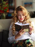 Happy young woman reading book at home Stock Image