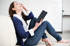Happy young woman reading book at home Stock Photography