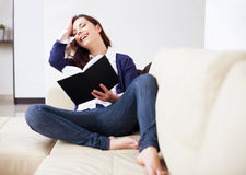 Happy young woman reading a book at home Royalty Free Stock Image