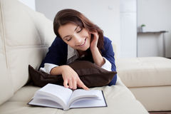 Happy young woman reading book at home Stock Photos