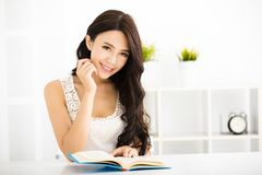 Happy young woman reading book Stock Photo