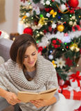 Happy young woman reading book near Christmas tree Stock Images
