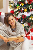 Happy young woman reading book near christmas tree Royalty Free Stock Image
