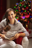 Happy young woman reading book near christmas tree Stock Photo