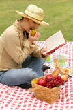 Happy Young Woman Reading Book Outdoor. Young girl reading book and eating apple in outdoor summer picnic stock photo