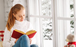 Happy young woman reading a book by window in winter royalty free stock image