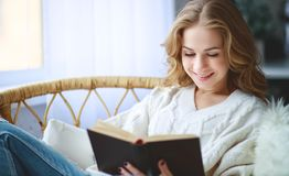 Happy young woman reading a book by window stock images