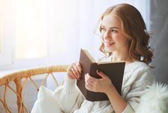 Happy young woman reading a book by window stock photos