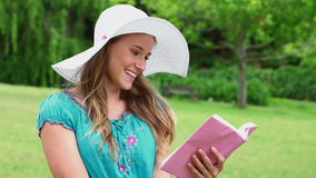 Happy young woman reading a fascinating book stock video