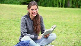 Happy young woman reading a fascinating novel. In a park stock video footage