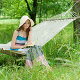 Happy young woman reading in hammock in green park outdoors Royalty Free Stock Photo