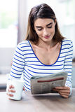 Happy young woman reading newspaper Royalty Free Stock Image