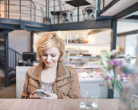 Happy young woman reading text message on cell phone in cafe Stock Photography
