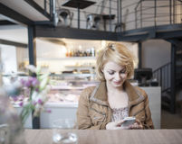 Happy young woman reading text message on cell phone in cafe Stock Images