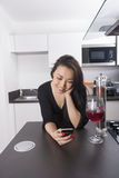Happy young woman reading text message on smart phone in kitchen Royalty Free Stock Photo