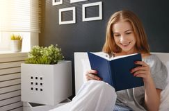 Happy young woman reads  book and drinks coffee in bed Stock Photos