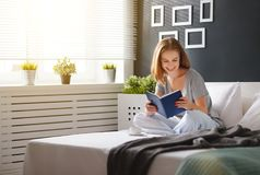 Happy young woman reads  book and drinks coffee in bed Stock Image