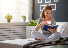 Happy young woman reads  book and drinks coffee in bed. Happy young woman reads book and drinks coffee in bed in   morning Stock Photo