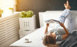 Happy young woman reads  book and drinks coffee in bed Stock Photo