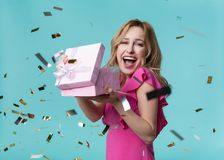 Happy young woman receiving present on celebration. Happy birthday. Portrait of joyful girl is opening gift box and shouting with excitement. Isolated Stock Photos