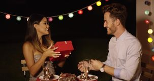 Happy young woman receiving a Valentines gift. Happy excited young woman receiving a Valentines gift from a handsome young man as they enjoy a romantic meal stock footage