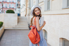 Happy young woman with red backpack walking on the street Royalty Free Stock Image