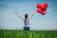 Happy young woman with a red balloon on a green meadow Royalty Free Stock Photography