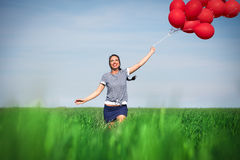 Happy young woman with a red balloon on a green meadow Stock Image