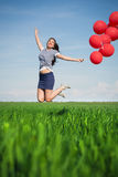 Happy young woman with a red balloon on a green meadow Stock Photo