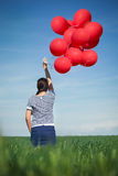 Happy young woman with a red balloon on a green meadow Stock Photography