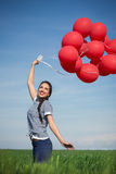 Happy young woman with a red balloon on a green meadow Royalty Free Stock Image