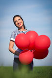 Happy young woman with a red balloon on a green meadow Royalty Free Stock Images