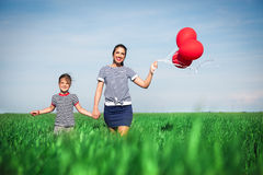 Happy young woman with a red balloon on a green meadow Stock Photos