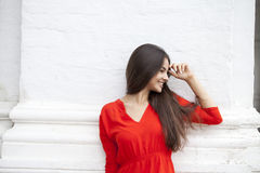 Happy young woman in red dress against the background of a block Royalty Free Stock Photography