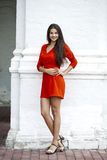 Happy young woman in red dress against the background of a block Royalty Free Stock Images