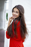 Happy young woman in red dress against the background of a block Stock Photography