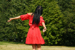 Happy young woman in red dress Stock Images