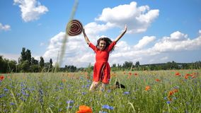 Happy young woman in red dress and big hat Enjoying Nature. Beauty Girl Outdoor walks on a poppy field. Freedom concept stock footage